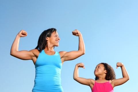 Mom and daughter flexing their muscles.