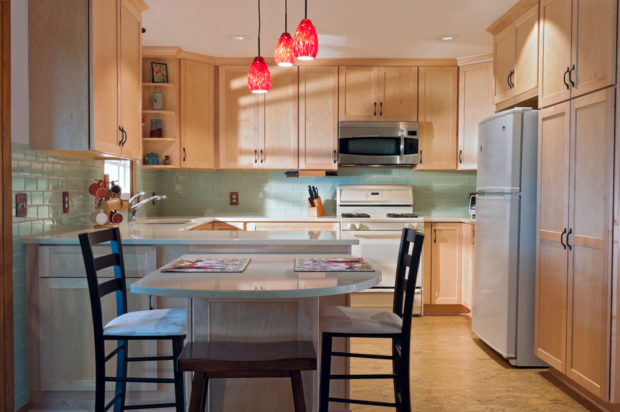 A newly remodeled kitchen interior with cork floors, maple cabinets, and a glass-tile backsplash. Pic: Shutterstock
