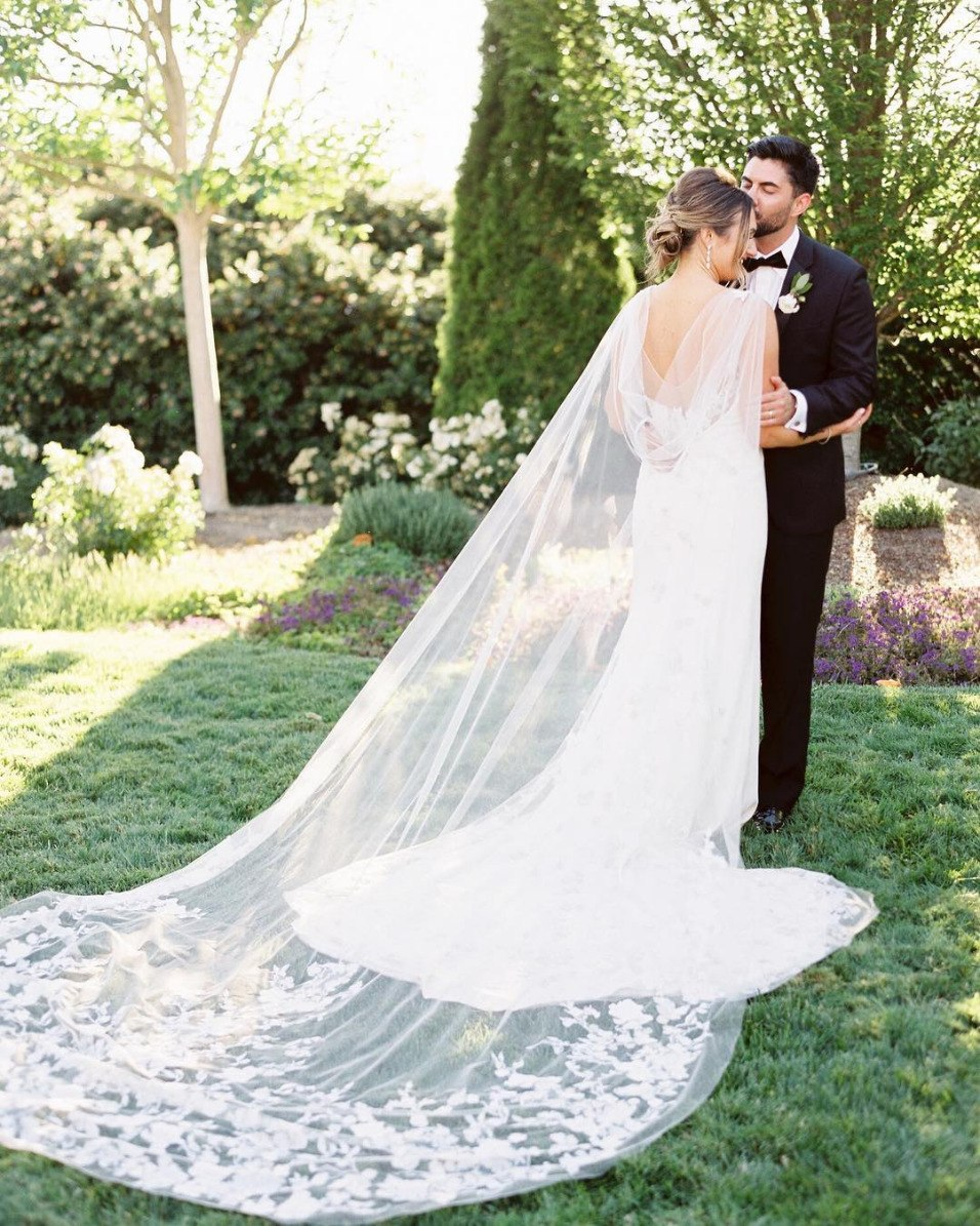 dramatic sheer wedding cape with bride and groom