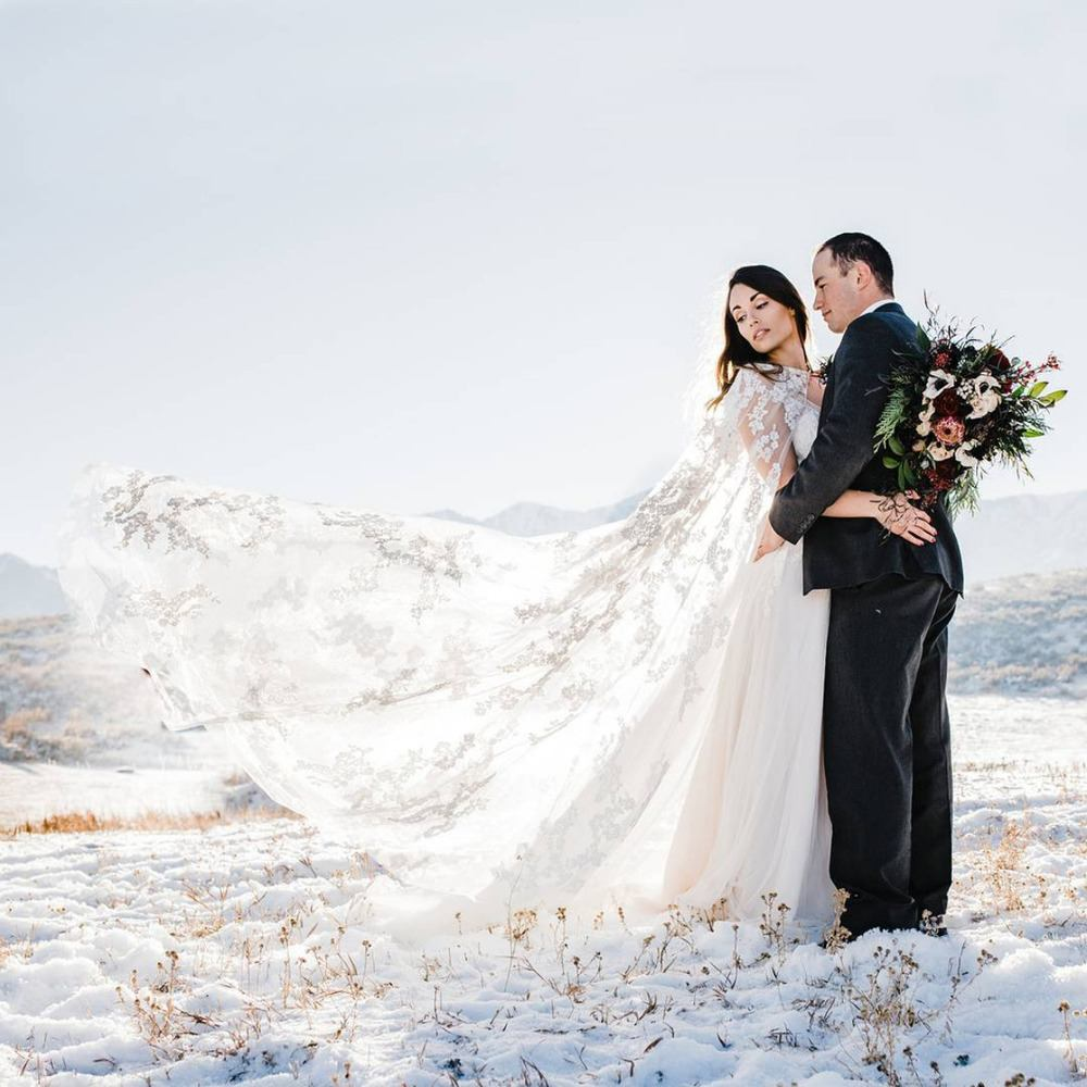 winter wedding bride and groom with lace bridal cape
