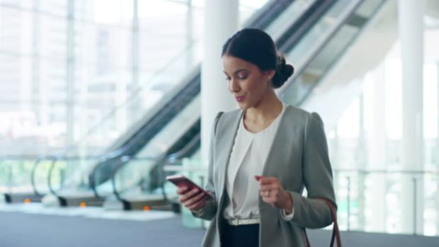 4k video footage of an attractive young businesswoman sending a text while walking through her office building